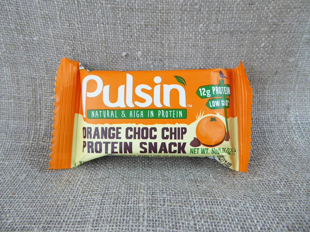 """Batonėlis """"Pulsin: Orange Choc Chip Protein Snack"""" (Su šokolado gabalėliais ir apelsinų aliejumi)"""